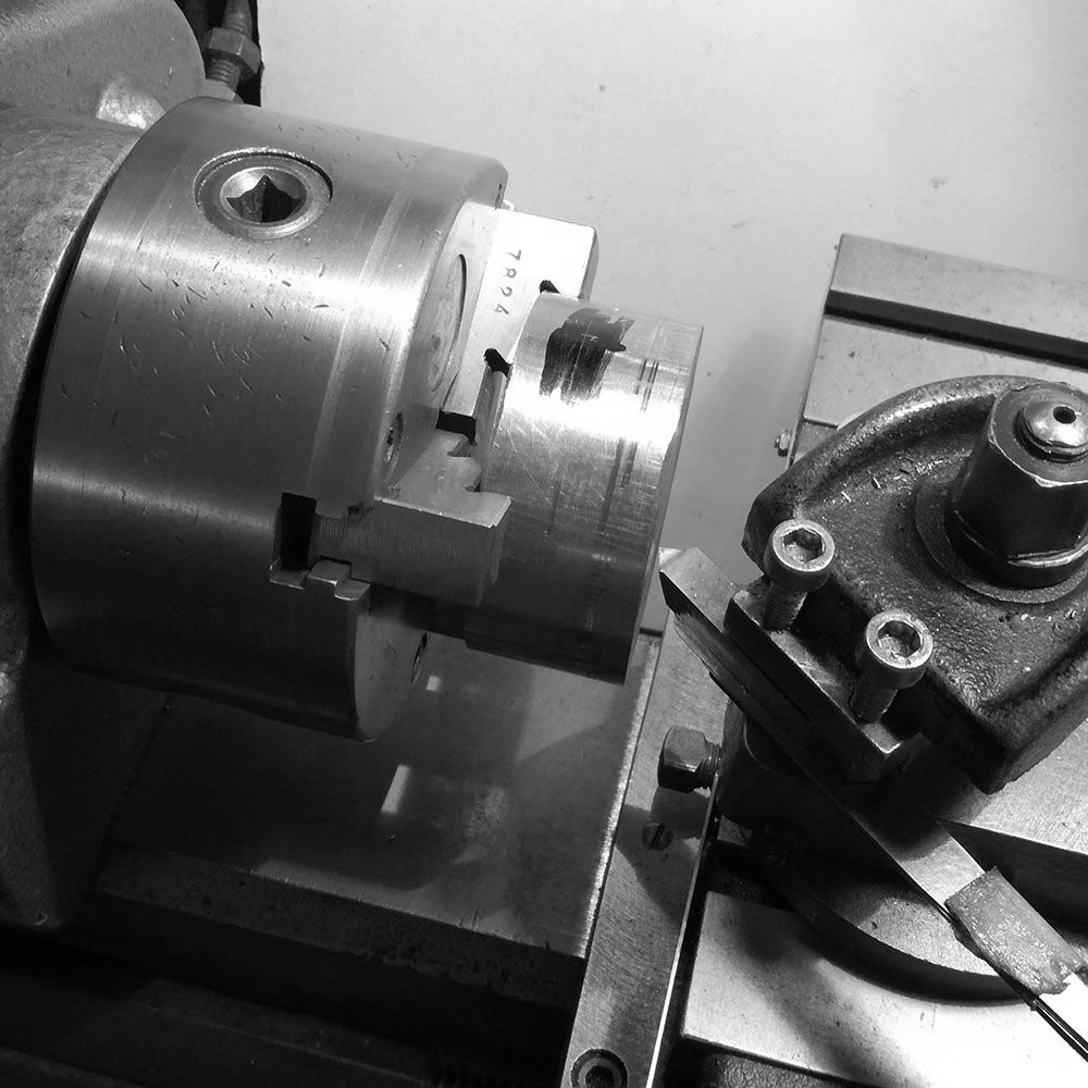 Since the billet is sawed off, both faces are not square to the sides, and if machined as such would not allow to repeatedly hold and get perpendicular surfaces on the lathe.