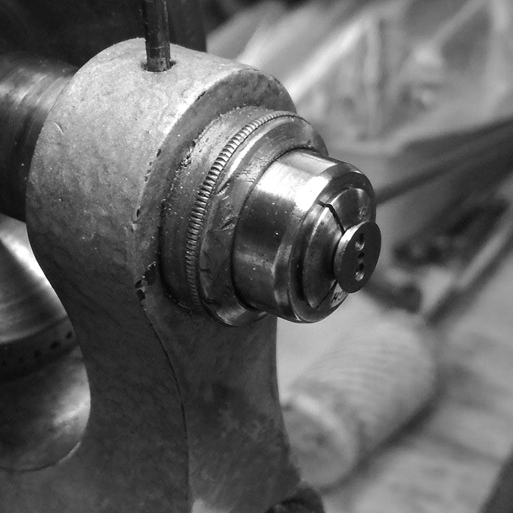 The rocking-lever cap is placed on a lathe to begin cleaning.